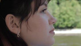 Πλάγια όψη του προσώπου της νέας ελκυστικής καυκάσιας γυναίκας με τα καφετιά μάτια απόθεμα βίντεο