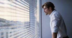 Πλάγια όψη του στοχαστικού νέου καυκάσιου αρσενικού ανώτερου υπαλλήλου που στέκεται κοντά στο παράθυρο στο σύγχρονο γραφείο 4k απόθεμα βίντεο