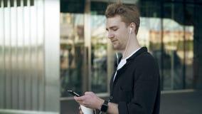 Πλάγια όψη του χαμογελώντας νεαρού άνδρα με το smartphone και του καφέ που ακούει τη μουσική απόθεμα βίντεο
