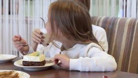 Πλάγια όψη - το γοητευτικό κορίτσι τρώει τη συνεδρίαση επιδορπίων δίπλα στην όμορφη νέα μητέρα απόθεμα βίντεο