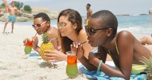 Πλάγια όψη των θηλυκών φίλων αναμιγνύω-φυλών που πίνουν τα ποτά κοκτέιλ στην παραλία 4k φιλμ μικρού μήκους