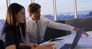 Πλάγια όψη των νέων καυκάσιων ανώτερων υπαλλήλων γραφείων που εργάζονται στο lap-top και το σχεδιάγραμμα στον πίνακα στο γραφείο  φιλμ μικρού μήκους