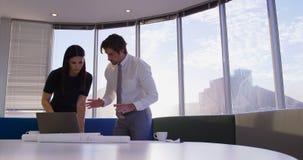 Πλάγια όψη των νέων καυκάσιων ανώτερων υπαλλήλων γραφείων που εργάζονται στο lap-top και το σχεδιάγραμμα στον πίνακα στο γραφείο  απόθεμα βίντεο