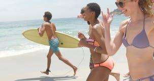 Πλάγια όψη των φίλων αναμιγνύω-φυλών που τρέχουν μαζί στην παραλία 4k φιλμ μικρού μήκους