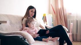 Πλάγια όψη, 4k: Η νέα ελκυστική μητέρα και η γλυκιά κόρη κάθονται στον καναπέ και την κατάρτιση απόθεμα βίντεο