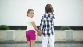 Πλάτη και διατήρηση στάσεων μερικών παιδιών τα χέρια τους Χαμογελώντας κυματίζοντας χέρι κοριτσιών απόθεμα βίντεο