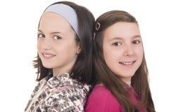 Πλάτη με πλάτη χαμόγελο δύο νέων κοριτσιών Στοκ Φωτογραφία