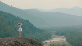 Πλάτη vie wfrom copter στον όμορφο ξανθό ταξιδιώτη που στέκεται στην άκρη των βουνών και που απολαμβάνει το τοπίο απόθεμα βίντεο