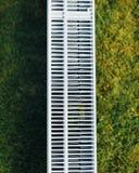 Πλέγμα θερμαντικών σωμάτων, πράσινο υπόβαθρο χορτοταπήτων, οικολογική έννοια θέρμανσης Στοκ Εικόνα