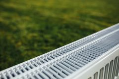 Πλέγμα θερμαντικών σωμάτων, πράσινο υπόβαθρο χορτοταπήτων, οικολογική έννοια θέρμανσης Στοκ Εικόνες