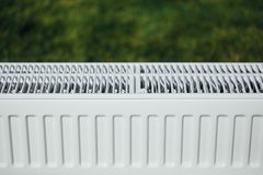 Πλέγμα θερμαντικών σωμάτων, πράσινο υπόβαθρο χορτοταπήτων, οικολογική έννοια θέρμανσης Στοκ Φωτογραφίες