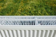 Πλέγμα θερμαντικών σωμάτων στον πράσινο χορτοτάπητα, οικολογική έννοια θέρμανσης Στοκ εικόνα με δικαίωμα ελεύθερης χρήσης