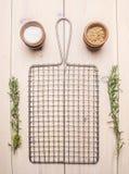 Πλέγμα μετάλλων για το μαγείρεμα με το δεντρολίβανο και τα καρυκεύματα στο άσπρο αγροτικό υπόβαθρο, θέση για το κείμενο Στοκ Εικόνες