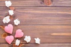Πλέκοντας ρόδινες καρδιές και άσπρα λουλούδια σε ένα ξύλινο υπόβαθρο Στοκ Εικόνες