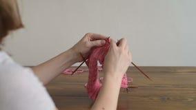 Πλέξιμο ενός ρόδινου καπέλου σε έναν ξύλινο πίνακα απόθεμα βίντεο