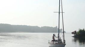 Πλέοντας βάρκα με τα πανιά κάτω από την ακτή προσεγγίσεων στη χαραυγή απόθεμα βίντεο