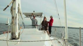 Πλέοντας, θηλυκοί και αρσενικοί ναυτικοί που εργάζονται στη γέφυρα του γιοτ απόθεμα βίντεο