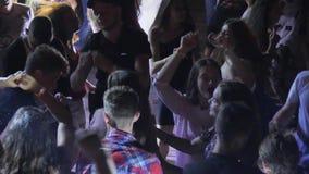 Πλήθος με τα χέρια που πηδούν επάνω στο νυχτερινό κέντρο διασκέδασης, κόμμα disco, νέοι που έχει τη διασκέδαση στη νύχτα, πολλή ν φιλμ μικρού μήκους