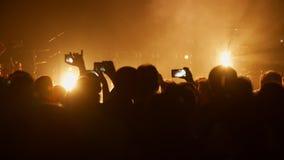 Πλήθος στα χέρια χειροκροτήματος συναυλίας, που παίρνουν τις φωτογραφίες και που καταγράφουν το βίντεο με τα smartphones απόθεμα βίντεο