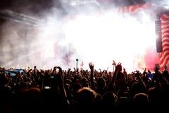 Πλήθος στη συναυλία - ενθαρρυντικό πλήθος μπροστά από τα φωτεινά ζωηρόχρωμα φω'τα σκηνών Στοκ φωτογραφία με δικαίωμα ελεύθερης χρήσης
