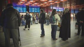 Πλήθος των επιβατών που περιμένουν στην αίθουσα σιδηροδρομικών σταθμών, που ελέγχει τα χρονοδιαγράμματα τραίνων απόθεμα βίντεο