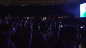 Πλήθος των ευτυχών ανθρώπων που τραγουδούν και που χορεύουν στη συναυλία, βίντεο μαγνητοσκόπησης στις συσκευές απόθεμα βίντεο