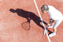 Πλήρες μήκος της ανώτερης παίζοντας αντισφαίρισης ατόμων στο κόκκινο δικαστήριο κατά τη διάρκεια του θερινού Σαββατοκύριακου στοκ εικόνες