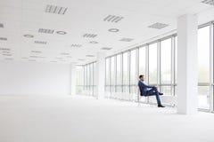 Πλήρες μήκος της στοχαστικής νέας συνεδρίασης επιχειρηματιών στην καρέκλα εξετάζοντας μέσω του παραθύρου το νέο κενό γραφείο στοκ φωτογραφία