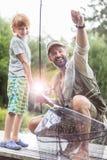 Πλήρες μήκος του χαμογελώντας πατέρα και του γιου που αλιεύουν στην αποβάθρα στοκ εικόνα με δικαίωμα ελεύθερης χρήσης