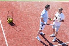 Πλήρες μήκος των ατόμων που μιλούν στεμένος στο γήπεδο αντισφαίρισης κατά τη διάρκεια της αντιστοιχίας στοκ φωτογραφίες με δικαίωμα ελεύθερης χρήσης
