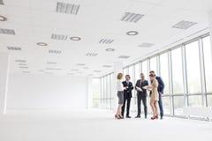 Πλήρες μήκος των επιχειρησιακών συναδέλφων που στέκονται συζητώντας στο νέο γραφείο στοκ φωτογραφία με δικαίωμα ελεύθερης χρήσης