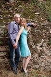 Πλήρες πορτρέτο ύψους του ευτυχούς ζεύγους με τη διαφορά ηλικίας που στέκεται στο πάρκο στο υπόβαθρο πετρών κατά τη διάρκεια του  Στοκ φωτογραφία με δικαίωμα ελεύθερης χρήσης