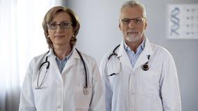 Πλήρης εμπιστοσύνης ομάδα γιατρών που εξετάζει με βεβαιότητα τη κάμερα, ποιοτική εγγύηση υπηρεσιών στοκ φωτογραφία