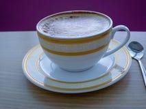 Πλήρης καφές στο φλυτζάνι και κουτάλι στον ξύλινο πίνακα Στοκ Φωτογραφίες