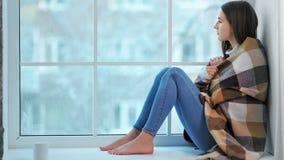 Πλήρης πυροβοληθείσα μελαγχολική νέα ξυπόλυτη συνεδρίαση γυναικών στο windowsill που εξετάζει τη χειμερινή σκηνή φιλμ μικρού μήκους
