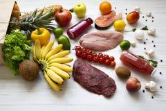 Πλήρης τσάντα εγγράφου των διάφορων υγιών τροφίμων πέρα από το άσπρο ξύλινο υπόβαθρο στοκ φωτογραφία με δικαίωμα ελεύθερης χρήσης