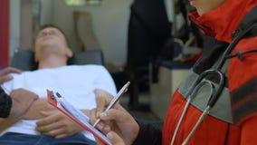 Πλήρωμα ασθενοφόρων που μεταφέρει τον ασθενή στο νοσοκομείο, θηλυκή τοποθέτηση γιατρών για τη κάμερα απόθεμα βίντεο