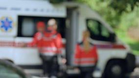 Πλήρωμα ασθενοφόρων που παίρνει στη μεταφορά, γρήγορα και την επαγγελματική βοήθεια, υπόβαθρο απόθεμα βίντεο