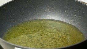 Πλήρως το φοινικέλαιο τροφίμων στο μαύρο τεφλόν τηγάνι βράζεται φιλμ μικρού μήκους