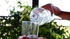 Πλήρωση ενός ποτηριού του καθαρού νερού Σε αργή κίνηση κινηματογράφηση σε πρώτο πλάνο ενός χύνοντας νερού γυναικών από ένα μπουκά