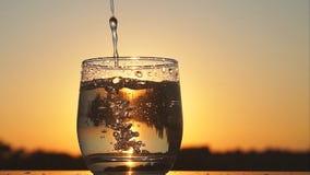 Πλήρωση του γυαλιού με το νερό στο ηλιοβασίλεμα, σε αργή κίνηση φιλμ μικρού μήκους