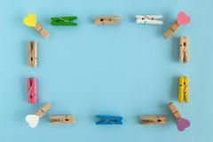 Πλαίσιο από τις ξύλινες ζωηρόχρωμες καρφίτσες με τις καρδιές στο μπλε υπόβαθρο με το διάστημα αντιγράφων Στοκ Εικόνες