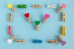Πλαίσιο από τις ξύλινες ζωηρόχρωμες καρφίτσες με τις καρδιές στο μπλε υπόβαθρο, τοπ άποψη Στοκ Εικόνα