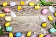 Πλαίσιο Πάσχας με τα χρωματισμένες αυγά, τα φτερά και την τουλίπα παλαιό σε ξύλινο Στοκ Εικόνα