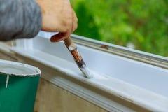 πλαίσιο παραθύρων ζωγραφικής με την άσπρη περιποίηση χρώματος στο σπίτι της στοκ φωτογραφία