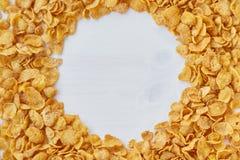 Πλαίσιο που ευθυγραμμίζεται στρογγυλό με τις νιφάδες καλαμποκιού Δημητριακά που διασκορπίζονται σε έναν ξύλινο πίνακα Στοκ Εικόνες