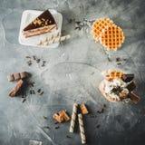 Πλαίσιο τροφίμων της σοκολάτας milkshake με τη στάζοντας σάλτσα, την κρέμα, το κέικ και το μπισκότο Επίπεδος βάλτε Τοπ όψη στοκ εικόνες