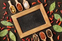 Πλαίσιο των διάφορων καρυκευμάτων στο σκοτεινό πίνακα πετρών στοκ φωτογραφίες