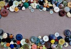 Πλαίσιο των διαφορετικών χρωματισμένων κουμπιών σε ένα γκρίζος-ρόδινο υπόβαθρο στοκ φωτογραφία με δικαίωμα ελεύθερης χρήσης