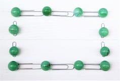 Πλαίσιο των πράσινων σφαιρών και του μετάλλου μαρμάρων paperclips, άσπρα ξύλινα υπόβαθρο και διάστημα αντιγράφων Στοκ Φωτογραφίες